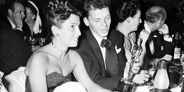 """In this March 11, 1946 file photo, at a crowded table at Ciro's, Frank Sinatra steals a glance at his Oscar which he won for his performance in the film """"The House I Live In,"""" as his wife Nancy looks on at left."""