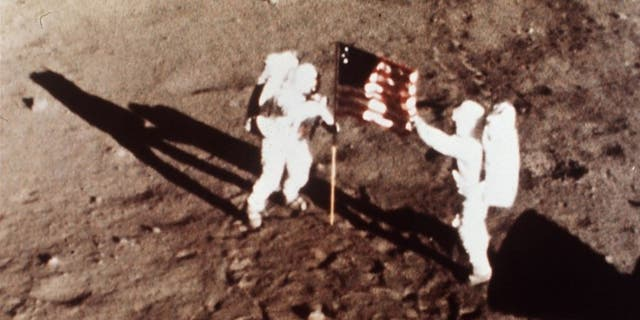 Apollo 11 astronauts Neil Armstrong and Buzz Aldrin plant an American flag on the surface of the moon in July 1969.