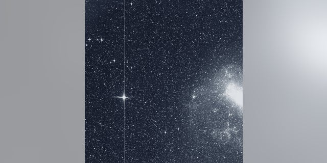 """The Transiting Exoplanet Survey Satellite (TESS) took this snapshot of the Large Magellanic Cloud (right) and the bright star R Doradus (left) with just a single detector of one of its cameras on Tuesday, Aug. 7. The frame is part of a swath of the southern sky TESS captured in its """"first light"""" science image as part of its initial round of data collection. (Credit: NASA/MIT/TESS)"""