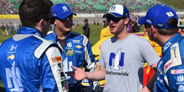 KANSAS CITY, KS - OCTOBER 16: Alex Bowman, driver of the #88 Nationwide Chevrolet, interacts with injured driver Dale Earnhardt Jr. on the grid prior to the NASCAR Sprint Cup Series Hollywood Casino 400 at Kansas Speedway on October 16, 2016 in Kansas City, Kansas. (Photo by Jason Hanna/Getty Images)