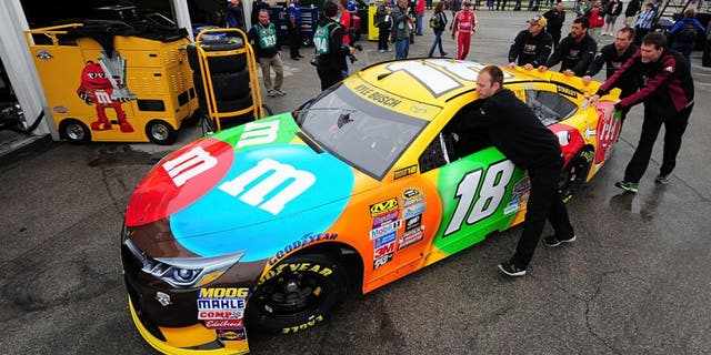 KANSAS CITY, KS - OCTOBER 14: Crew members push the #18 M&M's Toyota, driven by Kyle Busch, in the garage area prior to practice for the NASCAR Sprint Cup Series Hollywood Casino 400 at Kansas Speedway on October 14, 2016 in Kansas City, Kansas. (Photo by Jeff Curry/Getty Images)