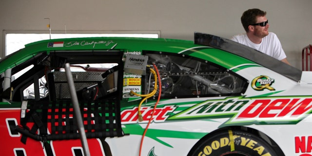 Dale Earnhardt Jr. peers out of the garage during NASCAR fuel-injection system testing at Daytona International Speedway in Daytona Beach, Fla., Tuesday, Nov. 15, 2011. (AP Photo/Daytona Beach News-Journal, Sean McNeil)