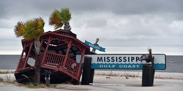 A gazebo is blown over the Mississippi Gulf Coast welcome sign near the intersection of Hewes Avenue and U.S. 90 in Gulfport, Miss., Sunday, Oct. 8, 2017.