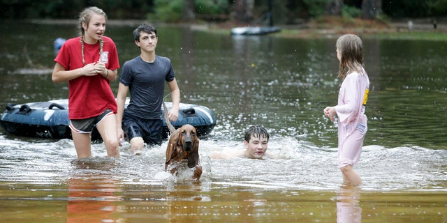 Crimson Peters, 7, right, Tracy Neilsen, 13, center right, Macee Neilsen, 15, left, and Tim Neilsen III, 16, center left, wade through the flood water the filled their front yard after Hurricane Nate, Sunday, Oct. 8, 2017, in Coden, Ala