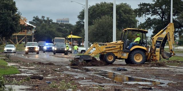 Biloxi public works employees clearing debris from U.S. 90 in Biloxi on Sunday.