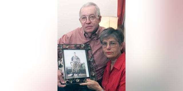 Will and Lynn Chapman holding a photo of their son, Sgt. 1st Class Nathan Ross Chapman, in 2002.