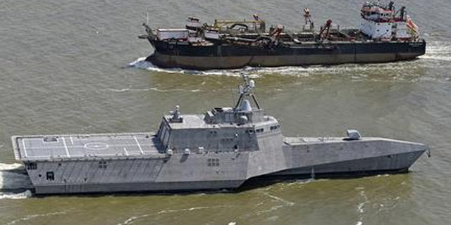 In this March 24, 2010, file photo, the littoral combat ship USS Independence, foreground, passes another vessel as it makes its way south through the waters of Mobile Bay, Ala.