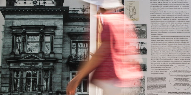 """File photo - A woman walks past an information board showing a picture of the villa that served as the headquarters for Nazi Germany's """"euthanasia"""" programme in Berlin, July 9, 2013. (REUTERS/Thomas Peter)"""