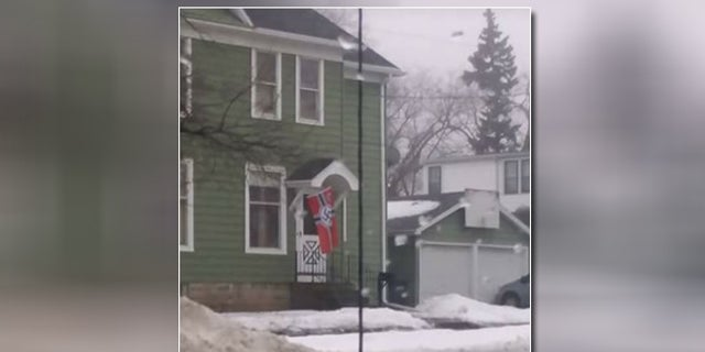 A family in Oshkosh, Wisc. says that this photo of their neighbor's Nazi flag created a firestorm after it went viral, leaving them no choice but to move after receiving numerous death threats.