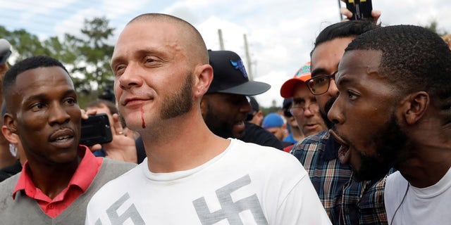 A man wearing a shirt with swastikas walks outside the location where white nationalist Richard Spencer gives a speech.