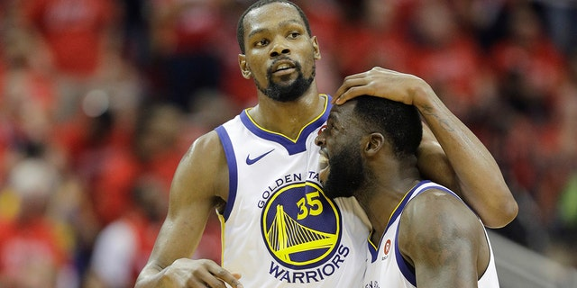 Golden State Warriors forward Kevin Durant (35) celebrates with teammate Draymond Green (23) during the second half in Game 7 of the NBA basketball Western Conference finals against the Houston Rockets, Monday, May 28, 2018, in Houston. (AP Photo/David J. Phillip)