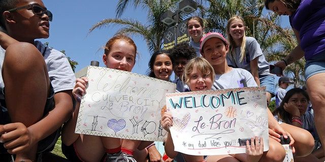Children from Culver City Teen Camp are seen holding signs as they wait for the arrival of LeBron James at Blaze Pizza.