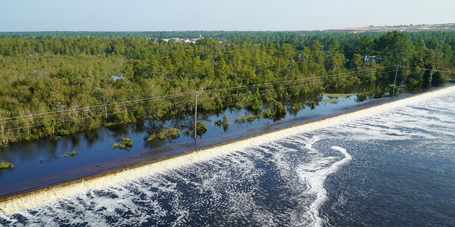 In this drone photo released by Duke Energy, flooding from the swollen Cape Fear River overtops an earthen dike at Sutton Lake, a 1,100-acre lake at the L.V. Sutton Power Station.
