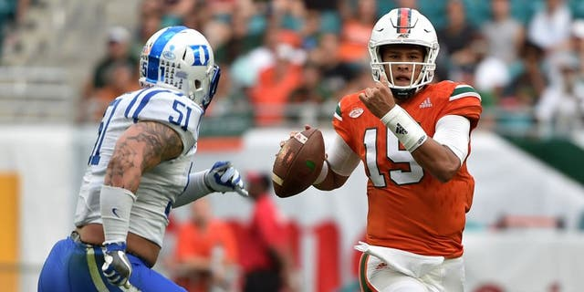 Nov 26, 2016; Miami Gardens, FL, USA; Miami Hurricanes quarterback Brad Kaaya (15) is pressured by Duke Blue Devils defensive end Dominic McDonald (51) during the first half at Hard Rock Stadium. Mandatory Credit: Steve Mitchell-USA TODAY Sports