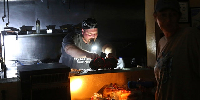 Aaron Howe cooks in the dark kitchen at the Island Convenience Store in Rodanthe on Hatteras Island, N.C., on Friday.