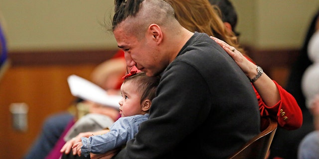 Ashston Matheny, boyfriend of murder victim Savanna LaFontaine-Greywind, holds their daughter, Haisley Jo, during the sentencing of Brooke Crews, in a Fargo, N.D., courtroom, Feb. 2, 2018.