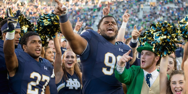 Notre Dame's leprechaun mascot celebrates with football players following a win in 2016.