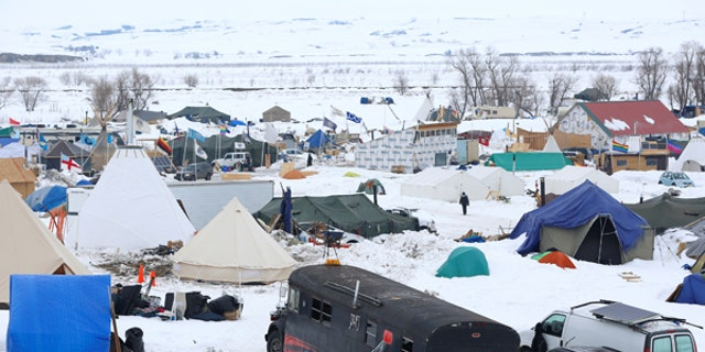 People walk through the Dakota Access Pipeline protest camp on the edge of the Standing Rock Sioux Reservation near Cannon Ball, N.D., on Jan. 24, 2017.