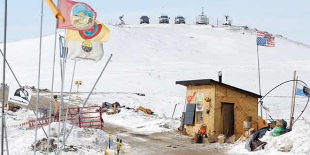 Police vehicles idle on the outskirts of the opposition camp against the Dakota Access oil pipeline near Cannon Ball, N.D., on Feb. 8, 2017.
