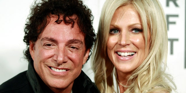 """Neal Schon of the band Journey arrives with Michaele Salahi for the premiere of """"Don't Stop Believin': Everyman's Journey"""" during the Tribeca Film Festival in New York, April 19, 2012."""