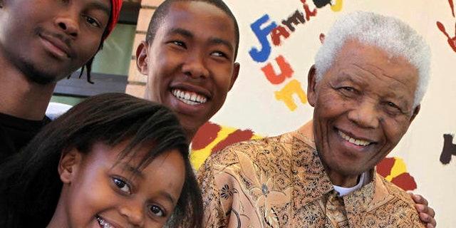 In this 2010 photo, Nelson Mandela, former South African president, right, is with his great-granddaughter Zenani Mandela, front left, Thembela Mandela, back left, and Mbuso Mandela, back right.
