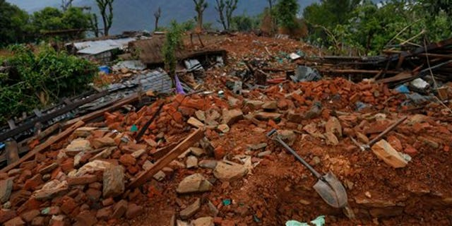 A shovel and pick lay on the rubble of a collapsed home destroyed village of Paslang near the epicenter of Saturday's massive earthquake in the Gorkha District of Nepal, Tuesday, April 28, 2015.  Military operations continue Tuesday to reach the isolated areas following the powerful earthquake that has devastated the nation and killed at least 4,400 people, according to district official Surya Mohan Adhikari. (AP Photo/Wally Santana)