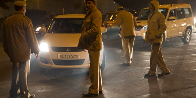Jan. 1, 2016: Indian policemen check passing cars on the New Year's eve in New Delhi, India. (AP)