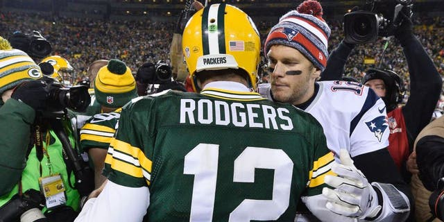 Tom Brady #12 of the New England Patriots (R) congratulates fellow quarterback Aaron Rodgers #12 of the Green Bay Packers after their game at Lambeau Field on November 30, 2014 a Green Bay, Wisconsin. The Packers defeated the Patriots 26-21. (Photo by Brian D. Kersey/Getty Images)