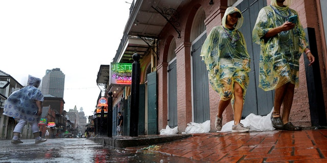 Tourists walk down Bourbon Street as Hurricane Nate approaches the U.S. Gulf Coast in New Orleans, Louisiana, U.S. on October 7, 2017.