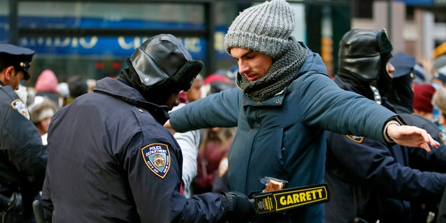 Dec. 31, 2014: A police officer checks a man entering a cordoned off area of Times Square on New Year's Eve in New York.