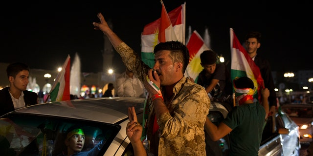 A man with 'yes' shaved into his hair chants through a speaker in the streets of Irbil after polling stations closed on Monday, Sept. 25, 2017. The Kurds of Iraq were voting in a referendum on support for independence that has stirred fears of instability across the region, as the war against the Islamic State group winds down.