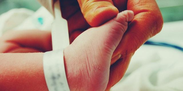 Holding My newborn Sons foot
