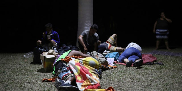 Central American migrants, who are participating in the annual Migrant Stations of the Cross caravan, go to sleep on the grass during the group's stop at a sports center in Matias Romero.