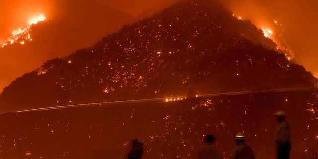 Firefighters monitor the Thomas fire as it burns through Los Padres National Forest near Ojai, Calif.