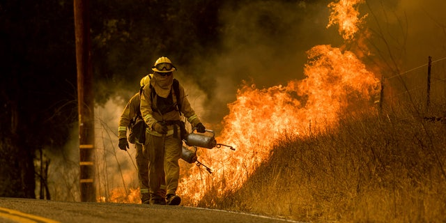 Firefighters light backfire while trying to keep a wildfire from jumping Santa Ana Rd. near Ventura, Calif.