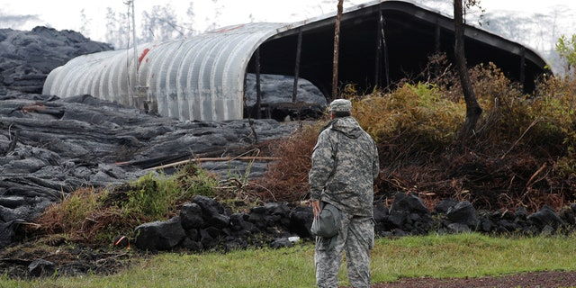 Maj. Jeff Hickman, of the Hawaii National Guard, stands near a structure destroyed by the Kilauea lava flow, in Leilani Estates near Pahoa, Hawaii, U.S., May 29, 2018.