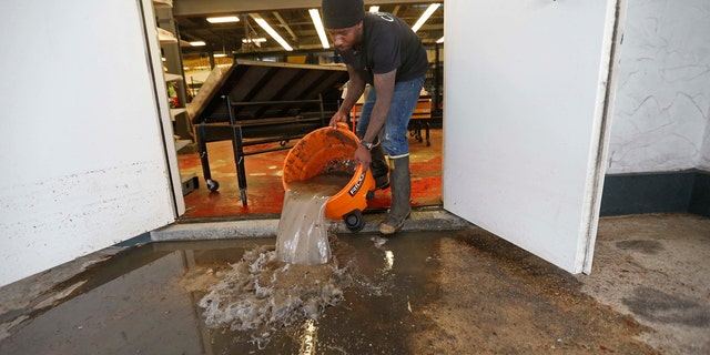 A man pours out water after a weekend of flooding.