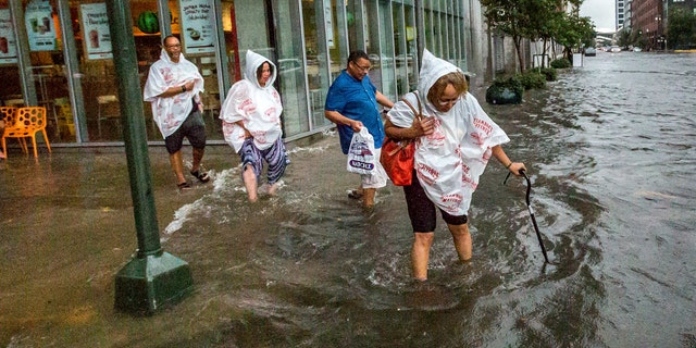 Philana Crite, of Cleveland who was in town for a family reunion, steps of the curb into flood waters in the New Orleans.