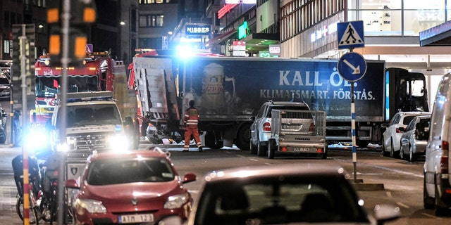 Tow trucks move a beer truck that crashed into the department store after plowing down the Drottninggatan Street in Stockholm.