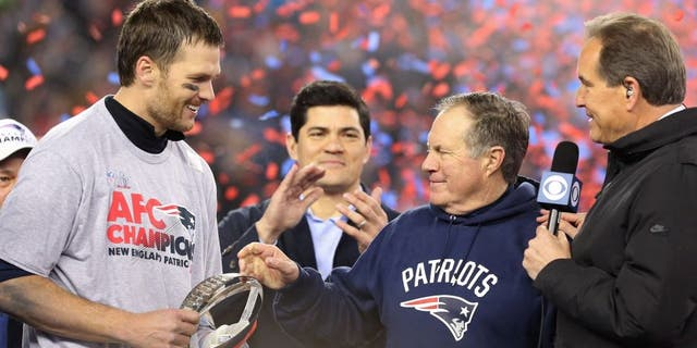 Jan 22, 2017; Foxborough, MA, USA; New England Patriots head coach Bill Belichick (M) hands the Lamar Hunt AFC championship trophy to Patriots quarterback Tom Brady (L) on the victory podium as CBS broadcaster Jim Nantz (R) looks on after the Patriots defeated the Pittsburgh Steelers in the 2017 AFC Championship Game at Gillette Stadium. Mandatory Credit: Geoff Burke-USA TODAY Sports