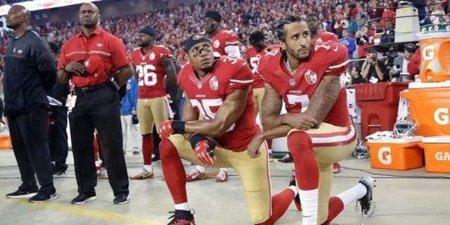 Colin Kaepernick and Eric Reid kneel during the national anthem