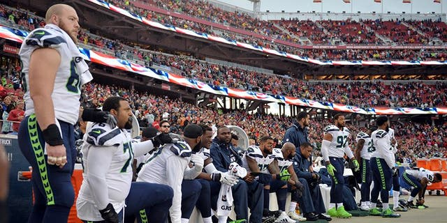 Seattle Seahawks players sit and kneel during the playing of the national anthem before a game against the San Francisco 49ers.