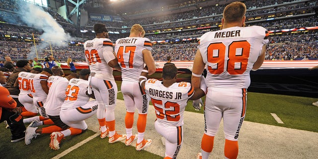 The Cleveland Browns team stand and kneel during the National Anthem before the start of their game against the Indianapolis Colts.