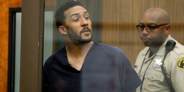 Former NFL football player Kellen Winslow Jr., center, looks through protective glass during his arraignment on Friday, June 15, 2018, in Vista, Calif.