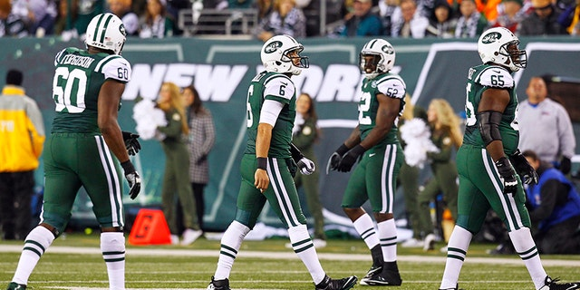 New York Jets quarterback Mark Sanchez (centre) walks off the field after his fumble led to another New England Patriots touchdown during their NFL football game in East Rutherford, New Jersey, November 22, 2012. REUTERS/Gary Hershorn (UNITED STATES  - Tags: SPORT FOOTBALL)   - TB3E8BN090NTE