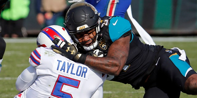 Jacksonville Jaguars defensive end Yannick Ngakoue, right, draws a penalty for a hit on Buffalo Bills quarterback Tyrod Taylor.