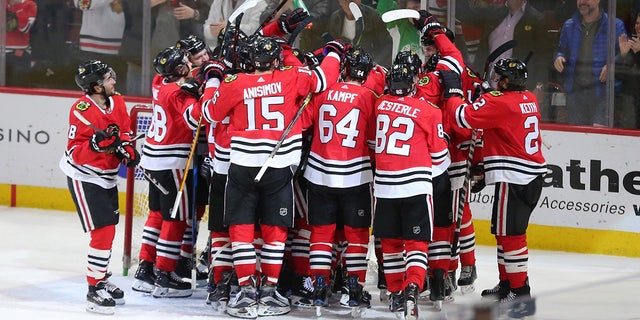 Blackhawks players gather around Scott Foster after the team's win Thursday night.