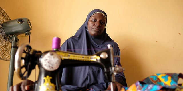 An unidentified internally displaced woman, who sews fabrics to sell, poses for a photograph in a community centre in Bama in northeast Nigeria, Nov. 23, 2017.