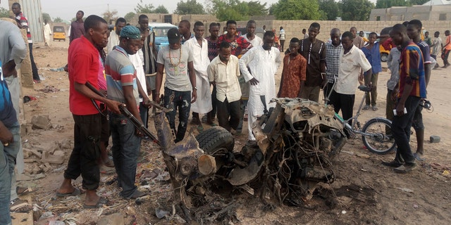 People gather at the site of a suicide bomb attack in Maiduguri, Nigeria Friday, April 27, 2018.