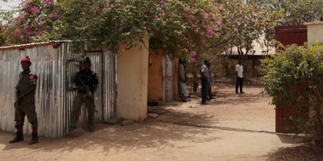 Security officers stand guard at the residence of abducted German archaeologists Johannes Behringer in Janjala Village, Nigeria.